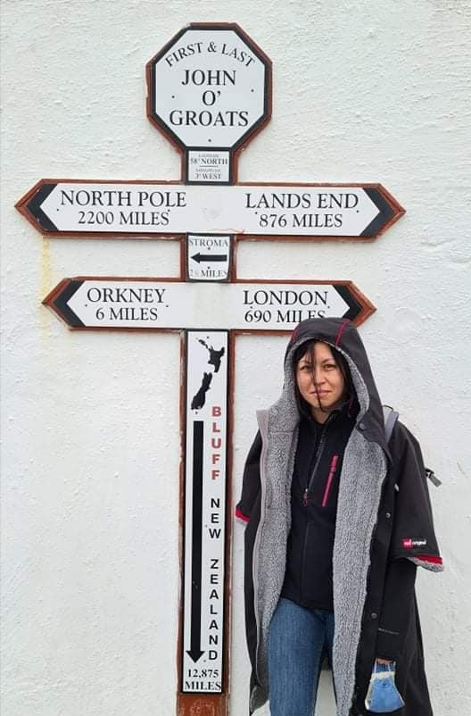 A woman stood in front of a signpost that points the way to Orkney Islands