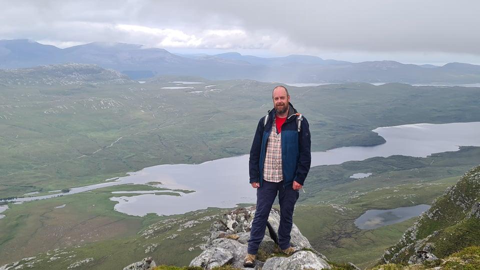A man stood on sheer cliffs above a dizzying drop