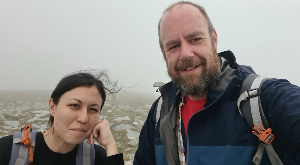 A man and a woman on a mist-covered summit