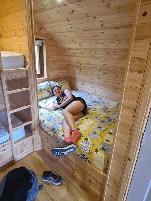 A woman lying on a bed in a small wooden hut