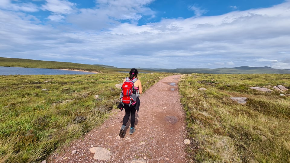A woman walking through moors and lochs along a path