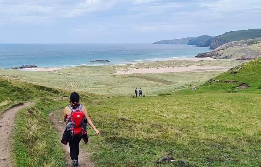 A woman walking towards a sandy beach over green hills