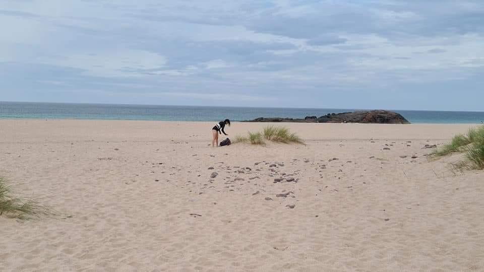A woman on a wide, sandy beach