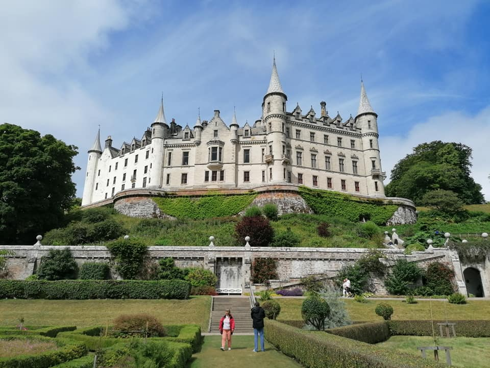 An imposing white castle with gardens sprawled beneath it
