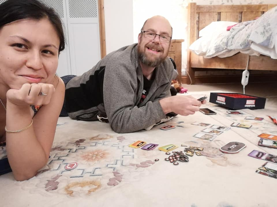 Two people playing a cardgame on the floor of a B&B room