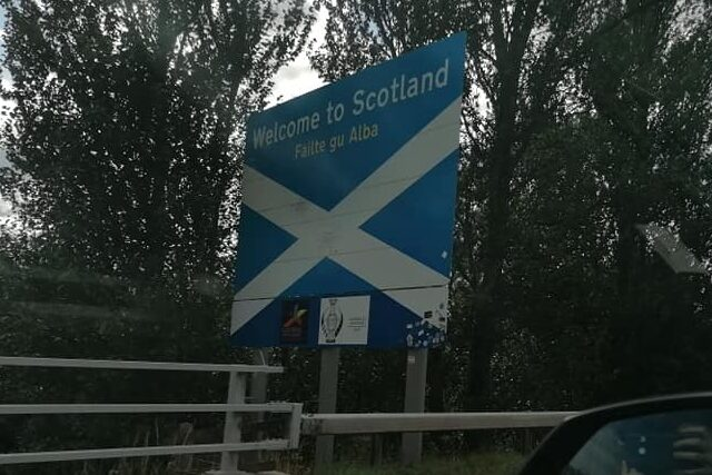 Photo of a roadsign painted like the Scottish flag, saying WELCOME TO SCOTLAND