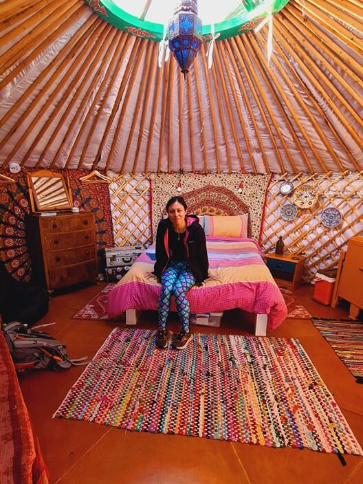 Woman sat on a bed in a colourful yurt