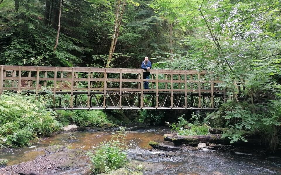 Man standing on a bridge above a river