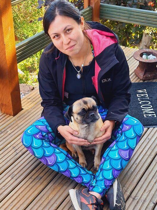 A woman cuddling a dog