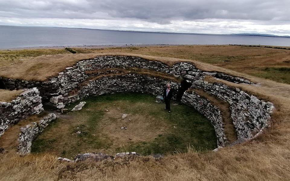 A man standing admist a ruined broch