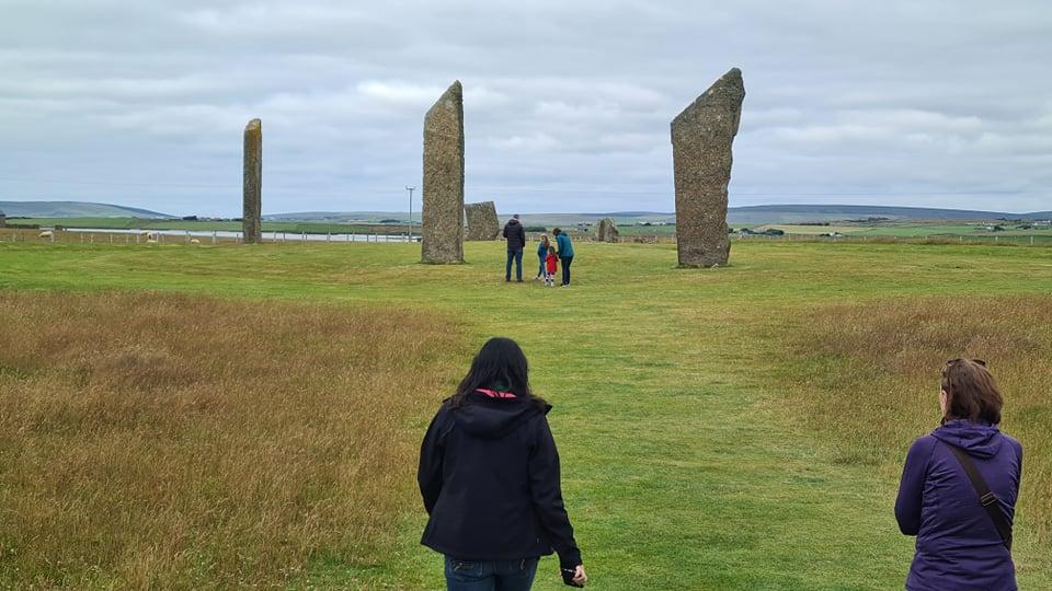 woman walking towards standing stones