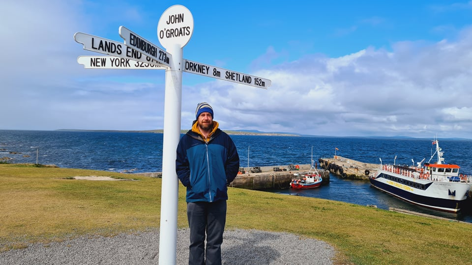 A man stood in front of a sign that says John O Groats