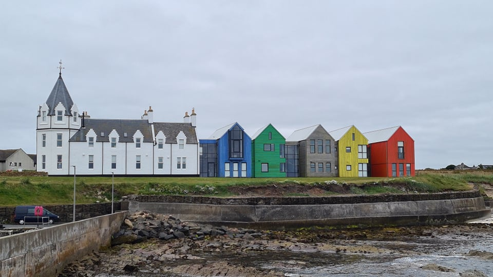 """A row of """"beach"""" houses painted in rainbow colours"""